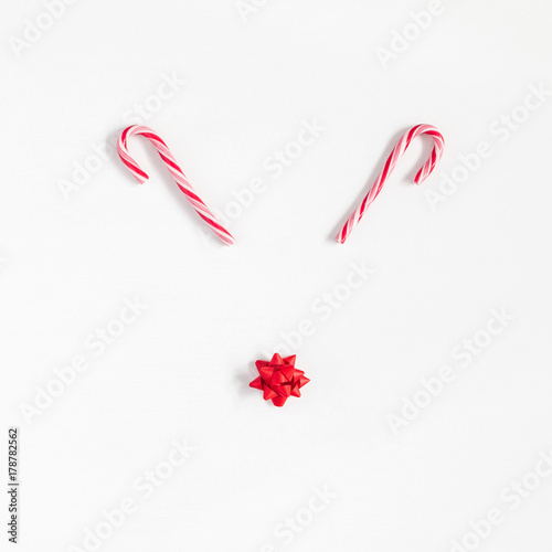 Fotobehang Hipster Hert Christmas decoration. Christmas deer made of candy canes and bow on white background. Flat lay, top view, square