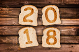 2018 greeting card toasted slices of bread on wooden planks background - 178785184