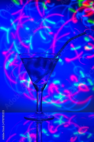 Leinwanddruck Bild Glass with a straw cocktail with ice against a backdrop of abstract illumination of colored neon