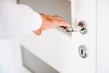 Door PVC. Hand holds doorknob. - 178786193