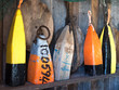 Colourful wooden nautical buoys neatly stacked on an antique shop shelve