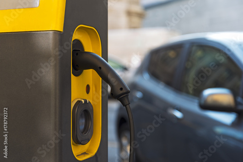 Electric car being charged at a public charge point Poster