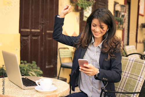 Fotobehang Muziek Young business woman listening music on smart phone at cafe.