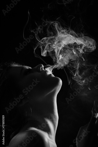 young woman with clouds of smoke smoking on black background, monochrome Poster
