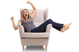 Tired young woman lying in an armchair and yawning - 178816180