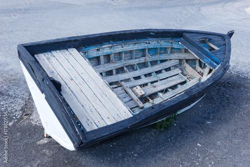 Aluminium Schipbreuk Old blue wooden boat on black sand at the beach