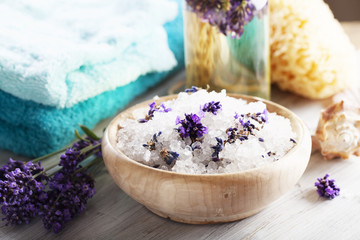 aromatherapy bath salt with lavender, bottle with massage oil in background