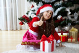 Celebration of Christmas, winter holidays and people concept. Happy young girl with gifts in boxes sitting near a decorated Christmas tree at home - 178833122