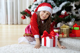 Celebration of Christmas, winter holidays and people concept. Happy young girl with gifts in boxes sitting near a decorated Christmas tree at home - 178833139