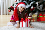 Celebration of Christmas, winter holidays and people concept. Happy young girl with gifts in boxes sitting near a decorated Christmas tree at home - 178833153