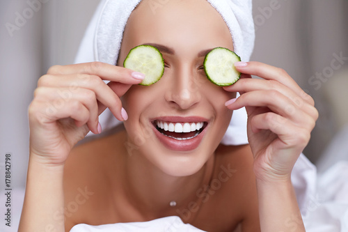 Leinwanddruck Bild Young beautiful smiling woman with towel on her head holding cucumber slices on the face. Skin care, spa and beauty Treatments. Anti aging cosmetics.