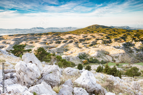 Fotobehang Wit After sunrise - the scenic view down from the highest mount (Pantocrator) on the Ionian Island Corfu, Greece. White rocks, beautiful autumn colors, maquis shrubland, blue sky.