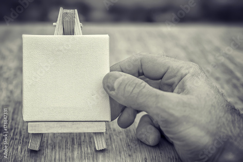 toy miniature easel in male hand. Black and white color. concept of art