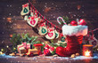 Leinwanddruck Bild - Advent calendar and Santa's shoe with gifts on rustic wooden background