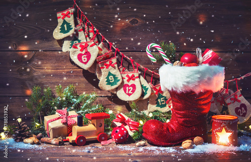 Leinwanddruck Bild Advent calendar and Santa's shoe with gifts on rustic wooden background