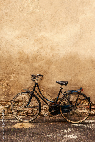 Fotobehang Fiets Verona. Retro styled image of vintage old Bicycle on Street in Italy, parking near wall with copy space.