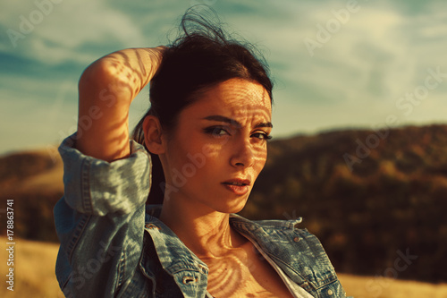 Portrait of a young woman with shadows texture on the face in a meadow with