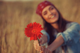 Beautiful young woman holding flower in a meadow. Focus on flower.