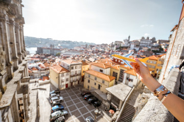 Holding a toy airplane on the Porto cityscape background. Traveling by airplane in Porto concept
