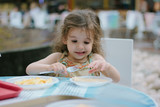 Little kid girl eating at the fast food restaurant - 178864348