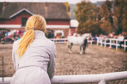 Blonde woman is watching a horse auction, English thoroughbred on a show Poster