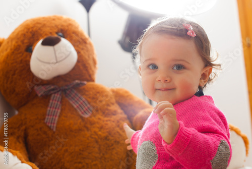 Toddler baby girl playing with big teddy bear