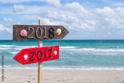 Metal 2018 and 2017 number on the wooden beach sign standing at the beach Poster