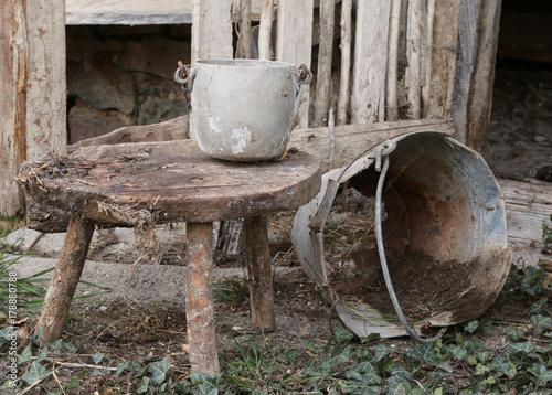 Poster old broken tin bucket and an aluminum pot over the stool