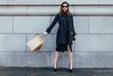 Stylish woman against wall with shopping bags - 178883972