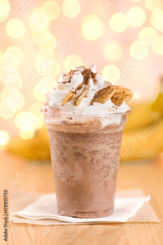 Foto op Aluminium Milkshake Banana cocoa in a plastic beaker to take out. Chocolate banana smoothie in glass with paper straw on wooden background, selective focus, horizontal, toned