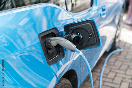 Blue electric car recharging on street with charge cable and plug leading to charge point.