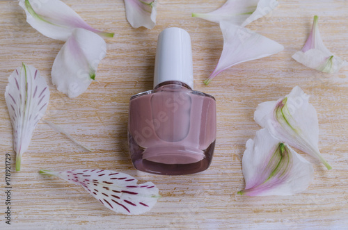 Fotobehang Pedicure Beige pink matte nail polish with flower petals on wooden background. Classic manicure color.