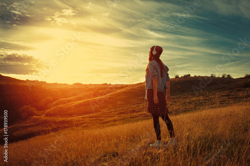 Young woman enjoys the sunset in nature