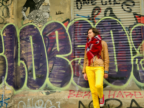 Fotobehang Graffiti Woman in yellow pants at the grafitti wall.
