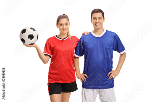 Female and male soccer players looking at the camera and smiling