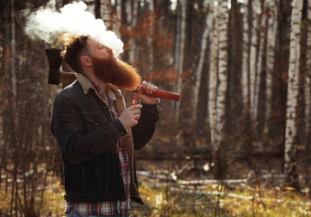 a woodcutter smokes an electronic cigarette after work