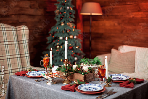 Beautiful Christmas family dinner table at the nicely decorated New Year interior with Christmas tree - 178967329