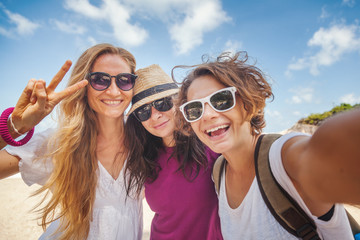 Young beautiful woman doing selfie on the beach. Friendship, freedom, travel.