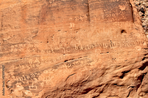 Inscription on red rocks in the valley on Wadi Rum desert in Jordan Poster