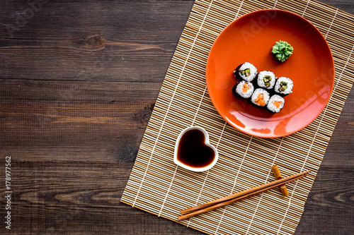 Fotobehang Sushi bar Sushi roll with salmon and avocado on plate with soy sauce, chopstick, wasabi on wooden table background top view copyspace