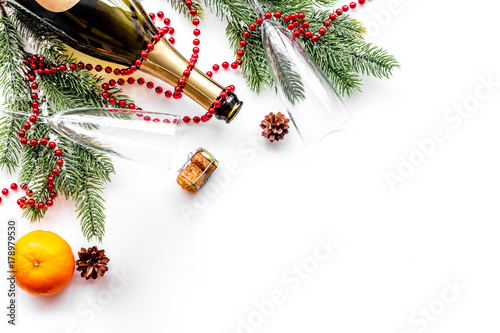 New year eve background. Spruce branch, glasses, champagne bottle, tangerines on white background top view copyspace
