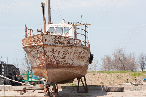 Fotobehang Schip Old fishing boat rusts on the shore