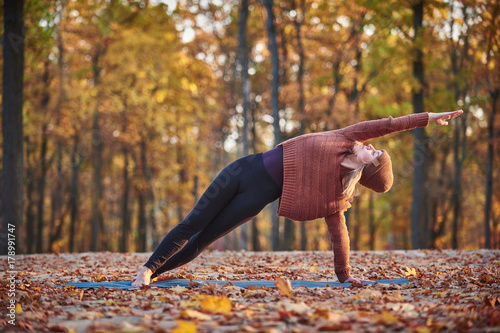 Wall mural Beautiful young woman practices side bend yoga asana Vasishthasana on the wooden deck in the autumn park