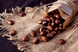 edible chestnuts - a bag of fresh, raw chestnuts sprinkled on the table - 178992313