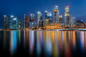 Singapore city downtown reflecting in water at Marina Bay