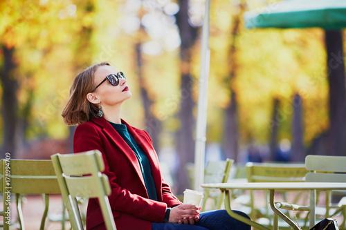 Plakat Elegant Parisian woman drinking coffee in park