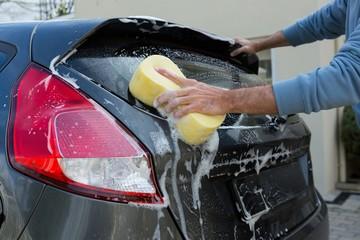 Auto service staff washing a car with sponge