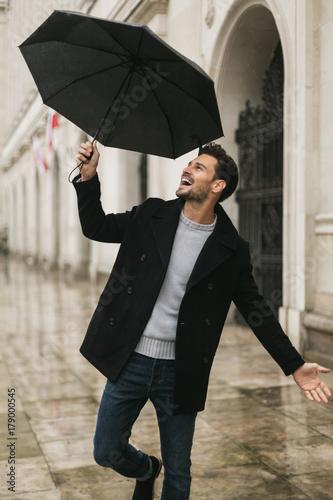 Juliste Handsome men dancing in the rain with an umbrella