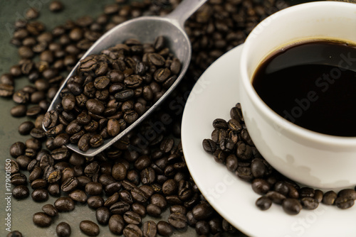 Papiers peints Cafe Hot coffee in the white cup with roast coffee beans and scoop on stone table background