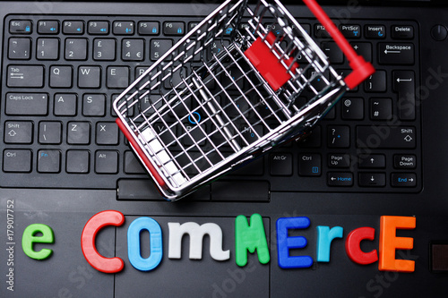 E-commerce text from colorful letters on laptop keyboard with metallic shopping trolley